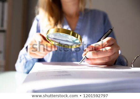 woman holding magnifying glass over invoice stock photo © andreypopov