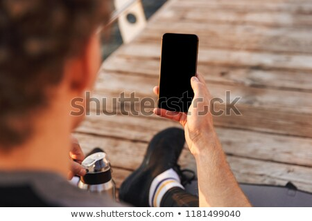 Сток-фото: Young Sports Guy Outdoors On The Beach Using Mobile Phone