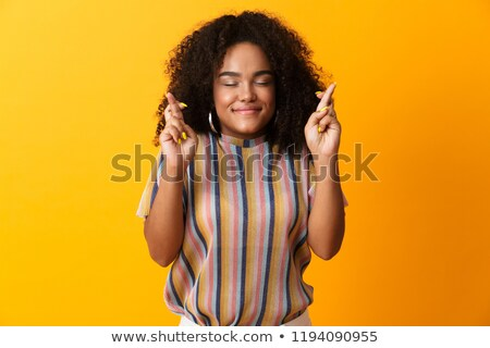 Stock photo: Excited young african cute girl posing isolated over yellow background make hopeful gesture.