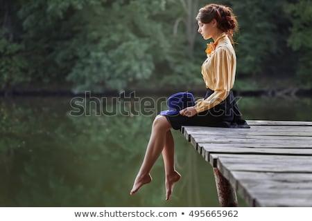 Fiatal nő ül móló tó naplemente víz Stock fotó © boggy