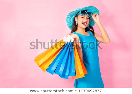Happy young asian beautiful woman posing isolated over blue background. Stock photo © deandrobot
