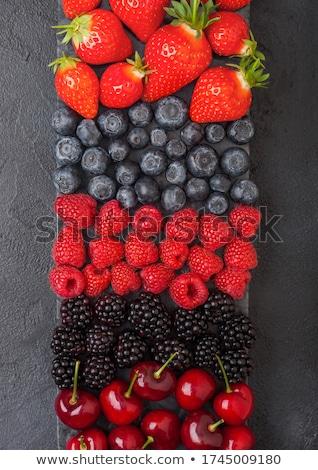 Fresh organic summer berries mix on black marble board on dark kitchen table background. Raspberries Stock photo © DenisMArt