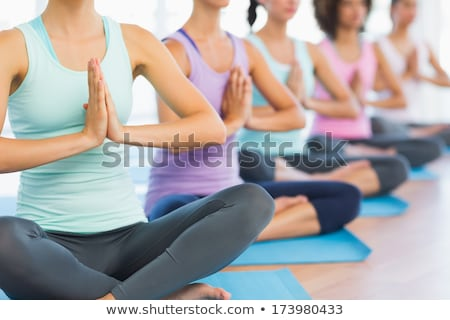 Concentrated young woman in sportswear sitting with crossed legs Stock photo © pressmaster