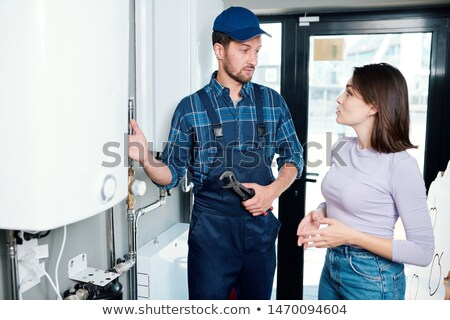 Young housewife consulting with technician of household maintenance service Stock photo © pressmaster