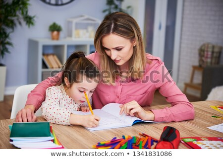 mother helping daughter with difficult homework Stock photo © dolgachov
