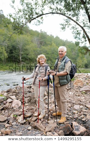 Happy mature man and woman with trekking sticks standing on stones Stock photo © pressmaster