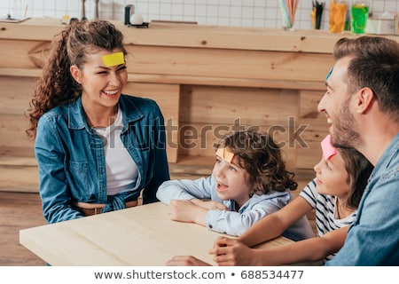 happy mother and daughter playing guess who game Stock photo © dolgachov