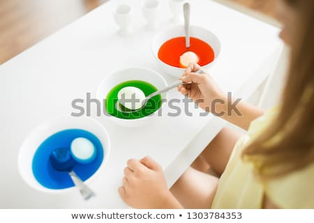 girl coloring easter eggs by liquid dye at home Stock photo © dolgachov
