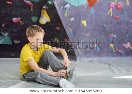 Schoolboy in activewear sitting on the floor in sports club and tying shoelace Stock photo © pressmaster