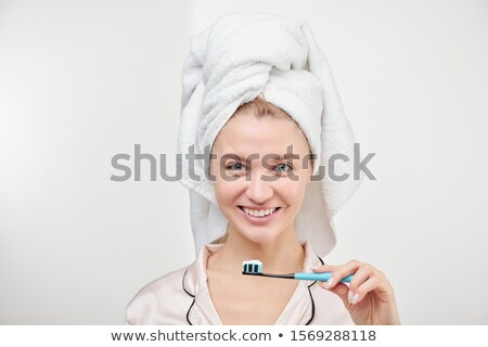 Cheerful young pretty woman with toothy smile holding toothbrush by her mouth Stock photo © pressmaster