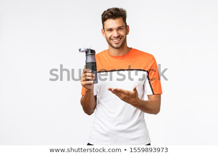 Fitness instructor holding water bottle and pointing at it as recommend drink after workout. Handsom Stock photo © benzoix