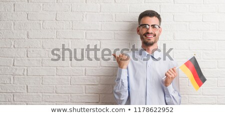 happy man showing thumbs up over german flag Stock photo © dolgachov