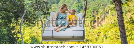 BANNER, LONG FORMAT Young boy swinging in the jungle rainforest of Bali island, Indonesia. Swing in  Stock photo © galitskaya