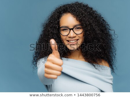 Portrait of dark skinned female has thumb up, shows agreement or approval, has smile on face, wears  Stock photo © vkstudio