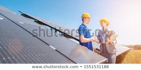 Construction worker and investor in solar power plant shaking hands Stock photo © Kzenon