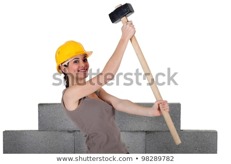 Woman lifting sledge-hammer in front of unfinished wall Stock photo © photography33