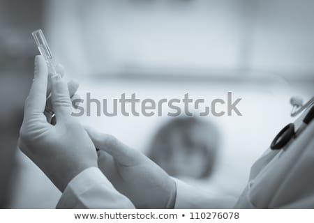 Doctor preparing a syringe in hospital ward in black and white stock photo © wavebreak_media