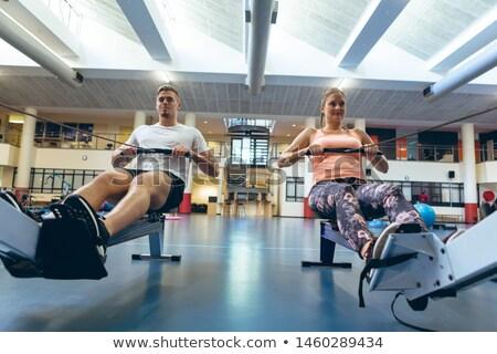 Woman on the rowing machine in fitness studio Stock photo © wavebreak_media