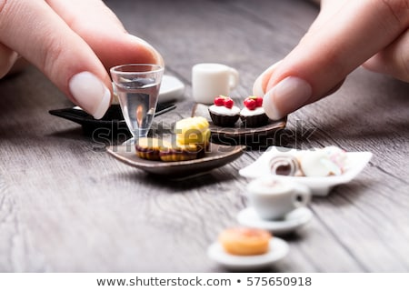 Stockfoto: Woman Picking Up A Cup Of Tea From A Table