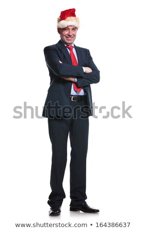 business man wearing santa hat and standing with hands crossed stock photo © feedough