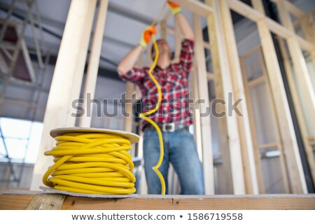 Electrician Fitting Wiring On Construction Site Stock photo © HighwayStarz