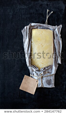 Mature cheddar cheese wrapped in rustic paper with a blank label. Stock photo © Photooiasson