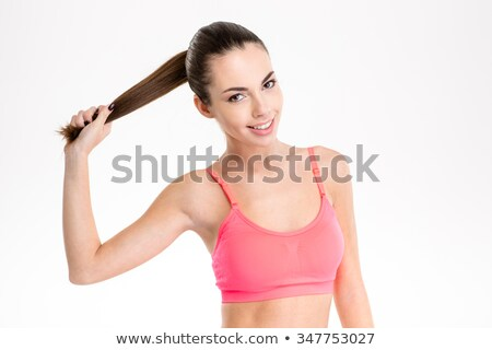 Happy fitness woman holding her hair in ponytail Stock photo © deandrobot