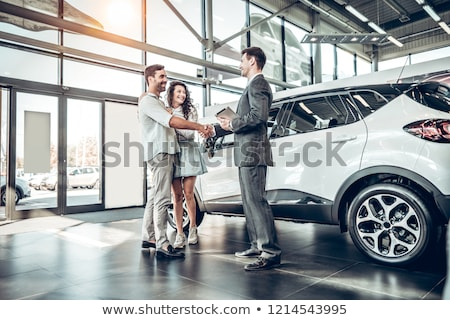 Stock photo: Smiling couple buying a car
