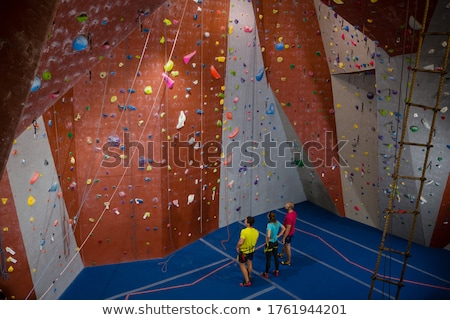Male trainer guiding athlete in climbing wall at health club Stock photo © wavebreak_media