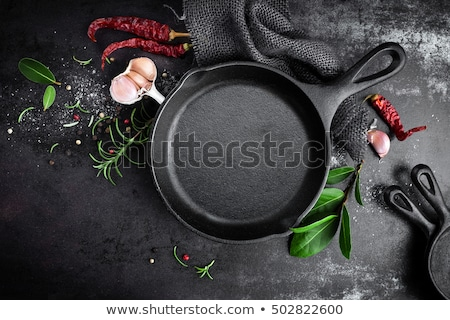 Empty cast-iron pan with ingredients for cooking on black background, top view Stock photo © yelenayemchuk