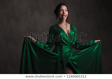 smiling brunette girl holding her green gown while standing Stock photo © feedough