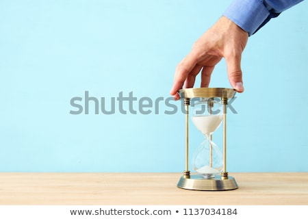 Businessman holding a hourglass. Concept of deadline in business Stock photo © alphaspirit