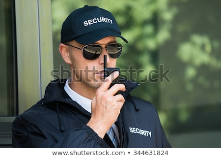 portrait of a security guard talking on walkie talkie stock photo © andreypopov