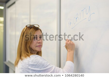 Businesswoman indoors writing on erasable board Stock photo © monkey_business