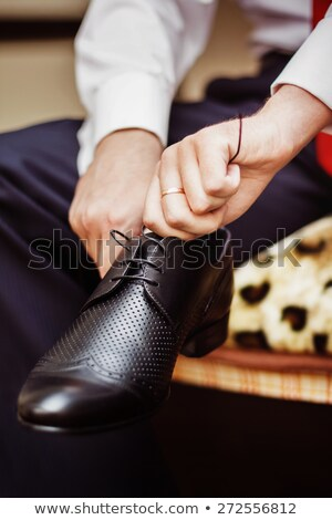 Close-up young man tying elegant shoes indoors Stock photo © ruslanshramko