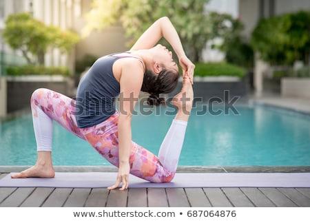 beautiful young happy woman doing yoga exercise near swimming pool healthy lifestyle and good welln stock photo © galitskaya