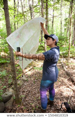 people looking at map finding their way in forest stock photo © robuart