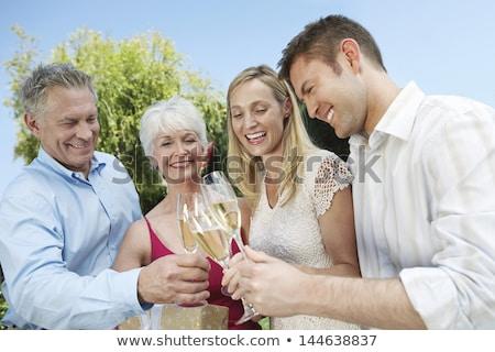 Volwassen mannen vrouwen fluiten champagne vieren Stockfoto © pressmaster