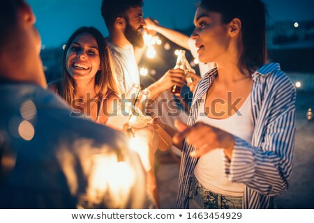 friends toasting party cups on rooftop at night Stock photo © dolgachov