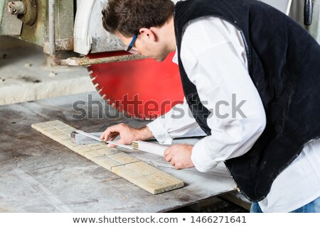 Handyman in stone carving factory at diamond saw Stock photo © Kzenon