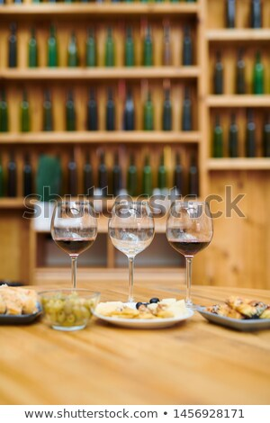 Three wineglasses and snack for sommelier on wooden table Stock photo © pressmaster