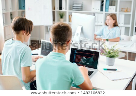Two boys by laptops and schoolgirl working over school project individually Stock photo © pressmaster