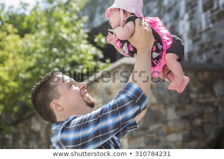 Dad throws baby up in a outside urban place Stock photo © Lopolo