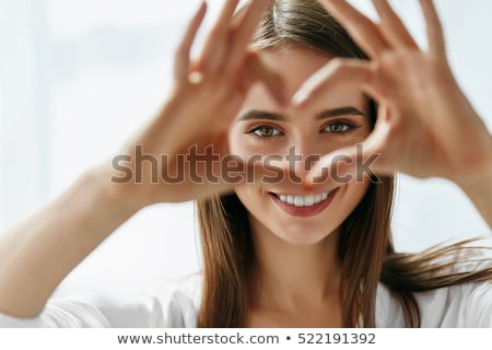 beautiful woman smiling and showing a heart stock photo © lichtmeister