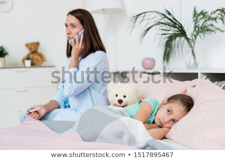 sick little girl lying on bed under blanket while her mother calling doctor stock photo © pressmaster