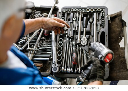 Hand of mature professional technician choosing nozzle from set of details Stock photo © pressmaster