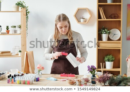Young woman in apron putting one of handmade soap bars into paper packet Stock photo © pressmaster