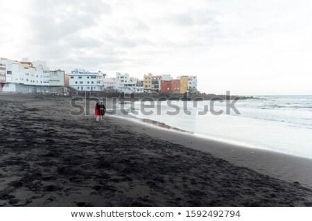 Couple in love walking on the beach near the powerful ocean with the sunset in Puerto de la cruz Stock photo © ruslanshramko