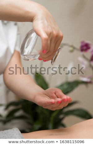 Masseuse puts massage oil in her hand Stock photo © boggy
