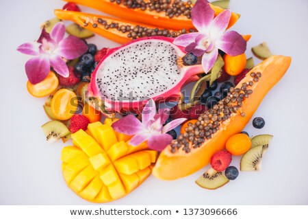 Fresh organic exotic fruits on white background. Ripe dargon fruit, papaya, kiwi, mango with kumquat Stock photo © vkstudio